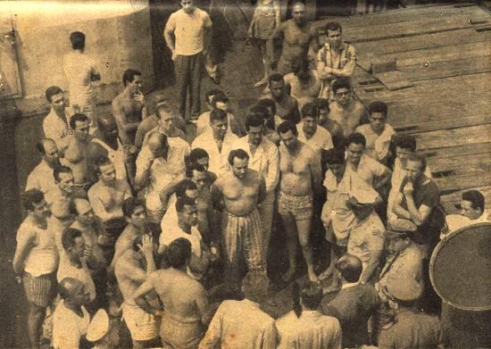 Os presos políticos no convés do navio ouvem os representantes da repressão.
