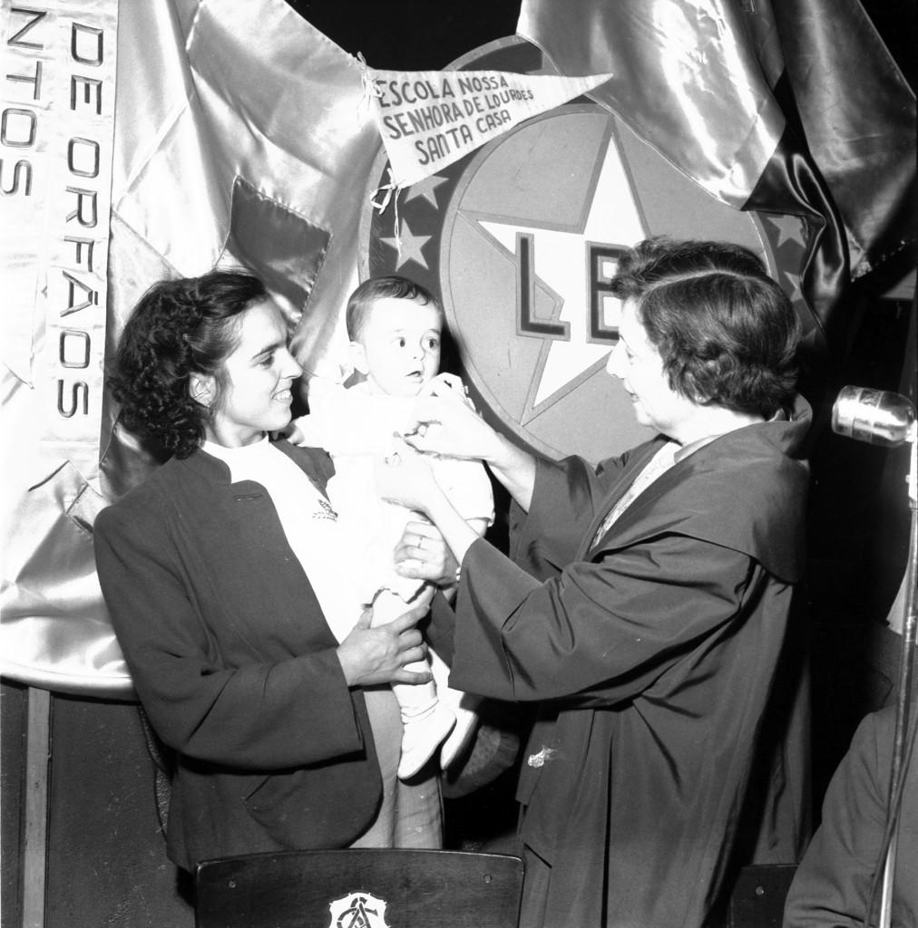 A presidente da Comissão de Santos da Legião Brasileira de Assistência (LBA), Marina Magalhães Santos Silva, premia uma das crianças.