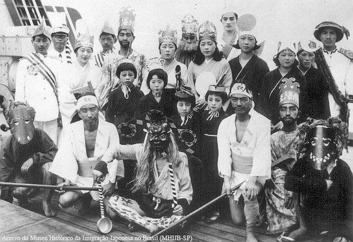 Uma bela cena da viagem ao Brasil, um grupo de imigrantes vestidos com coroas, máscaras e kimonos para o Sekido Matsuri no vapor La Plata Maru. Pode-se observar as máscaras, provavelmente estes são aqueles que estão no papel de oni.