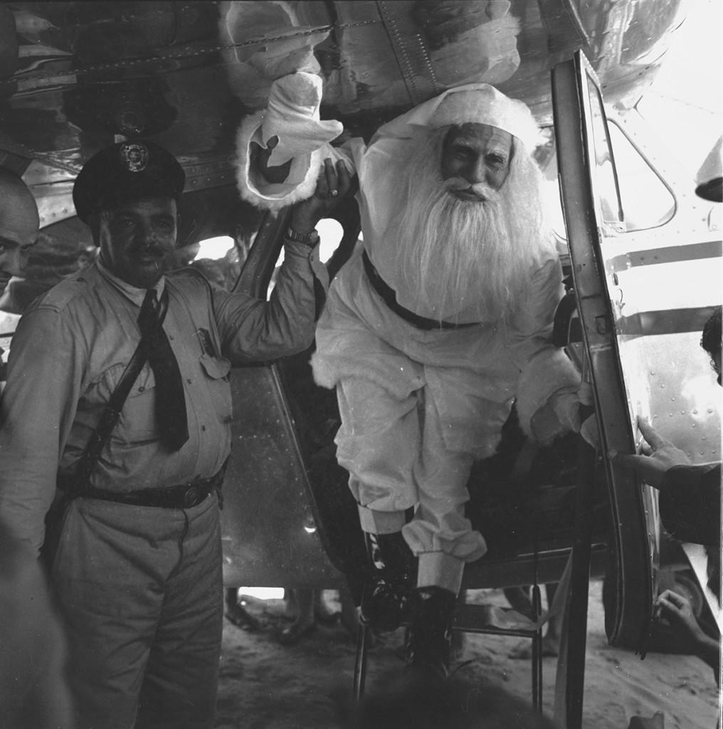 """Papai Noel de 1957, chegando de avião. Na recepção, o popular guarda civil Mussi, o """"bigode""""."""