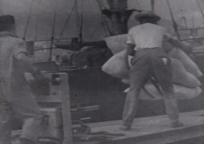 Cenas de embarque de cargas no porto, na época do trabalho braçal.