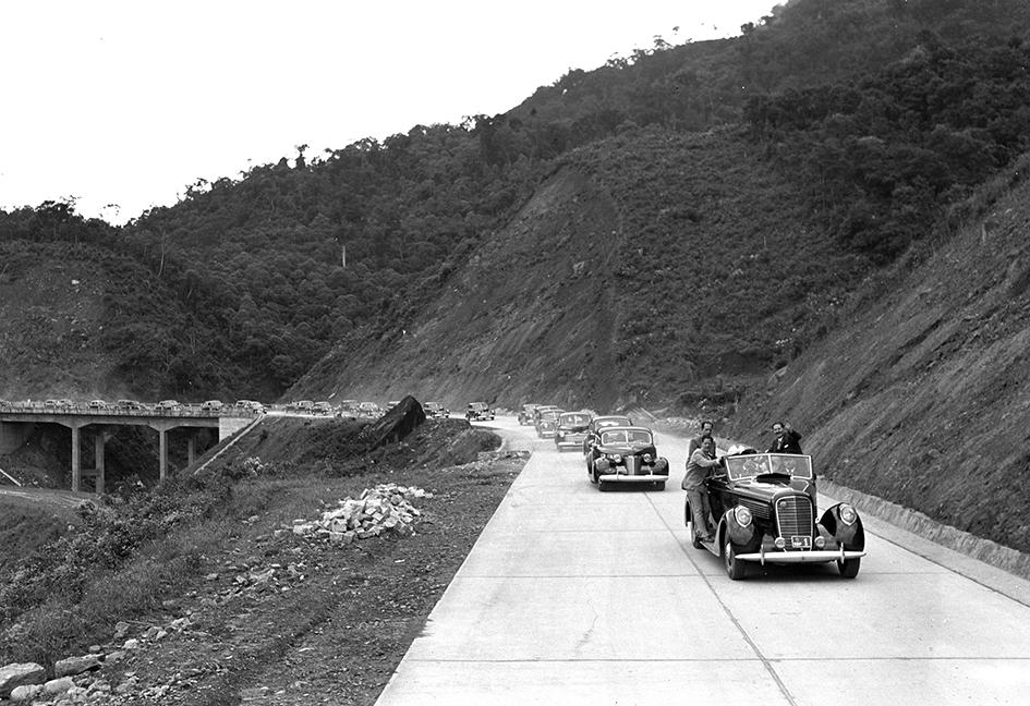 O governador Ademar de Barros vem no carro da frente, puxando o comboio festivo da inauguração da primeira pista da Via Anchieta em abril de 1947.