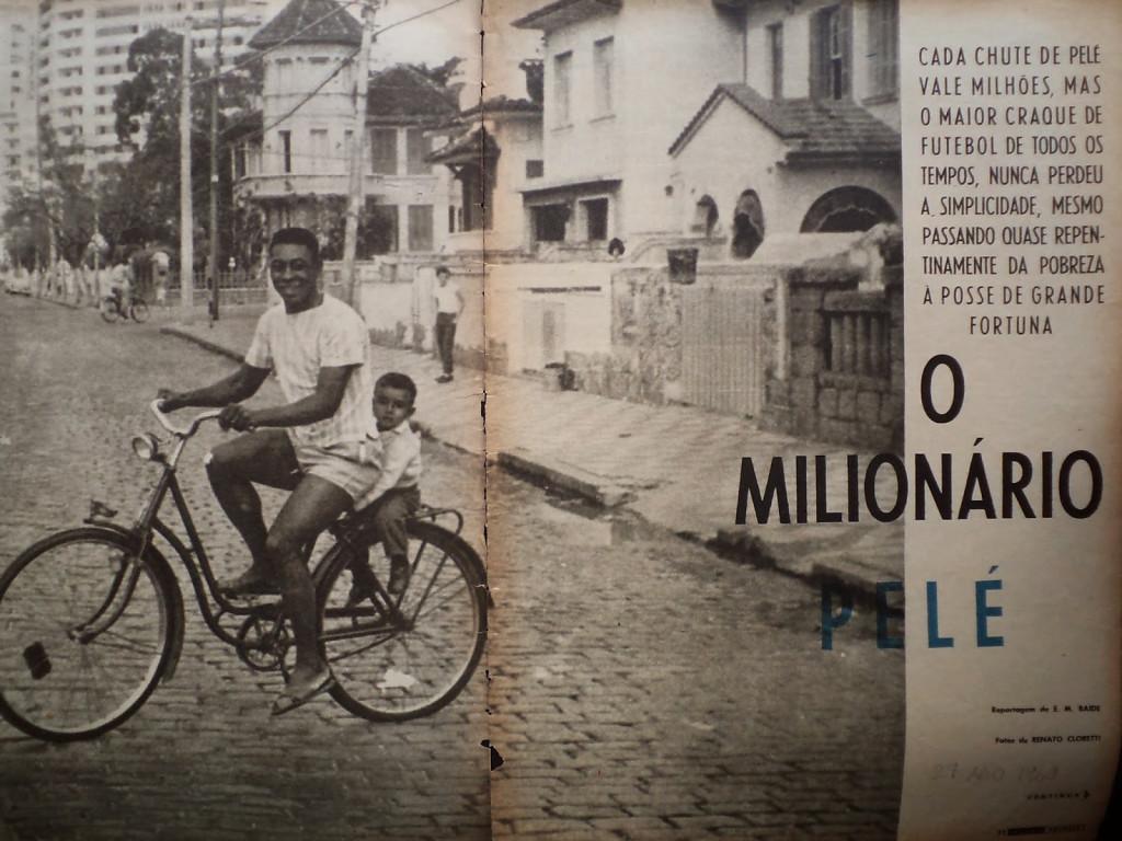 """Pelé pedala na Avenida Pinheiro Machado, defronte à Pensão de Raimundo, com bicicleta emprestada. Na garupa, o menino """"Porunguinha"""", de três anos de idade, espécie de irmão adotivo de Edson Arantes do Nascimento."""