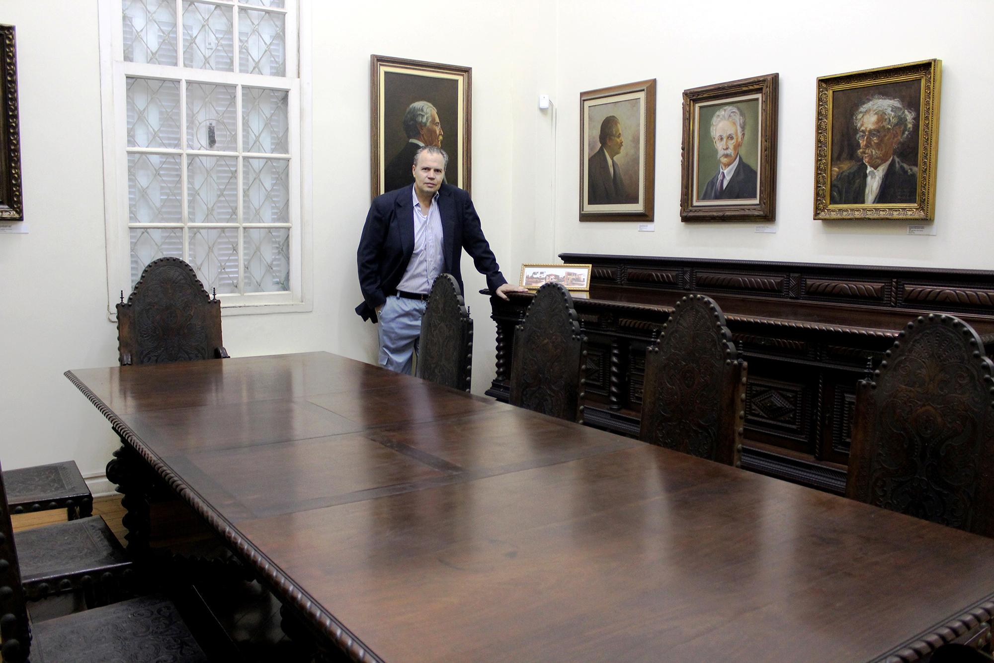 Thiago Bellegarde Patti de Souza Varela, neto de Manoel Varela, ao lado da mesa original da sala de jantar de seu avô, que foi doada para a Fundação Pinacoteca Benedito Calixto.