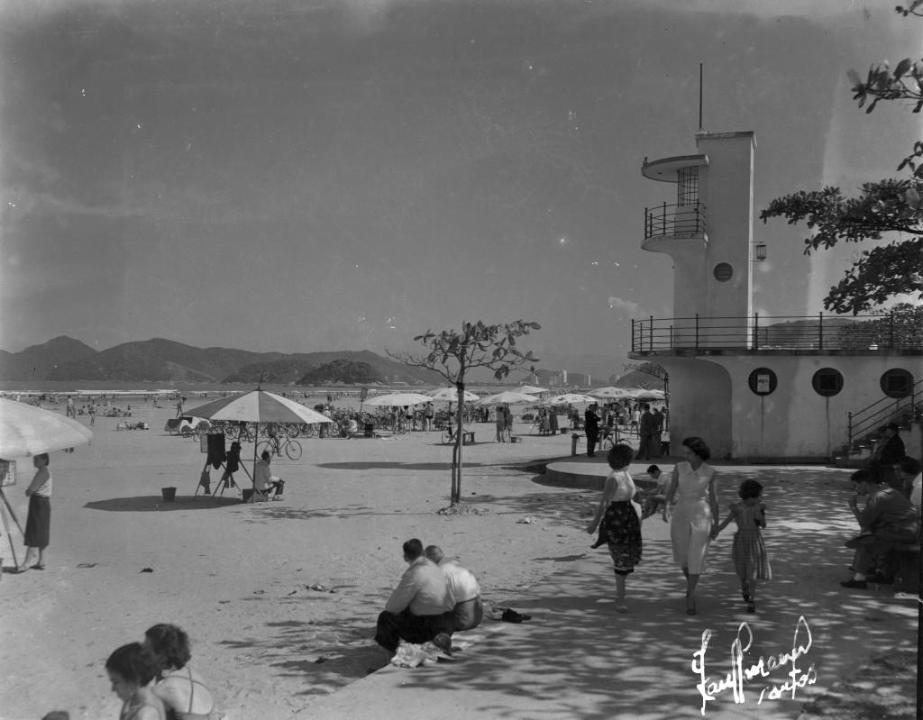 Ao longo da orla santista, em especial na faixa de areia, ficavam os fotógrafos lambe-lambes, como o visto nesta imagem dos anos 1950, do fotógrafo Boris Kaufmann. Os profissionais ficavam embaixo de guarda-sóis aguardando os seus clientes.