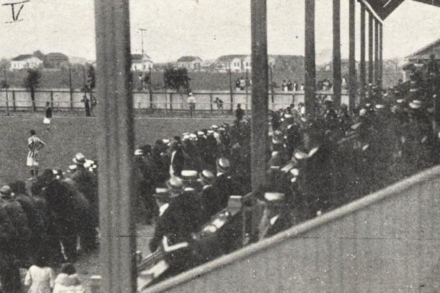 Arquibancada o campo do Santos FC lotada de torcedores. Interessante notar que praticamente todos fazem uso de chapéu.